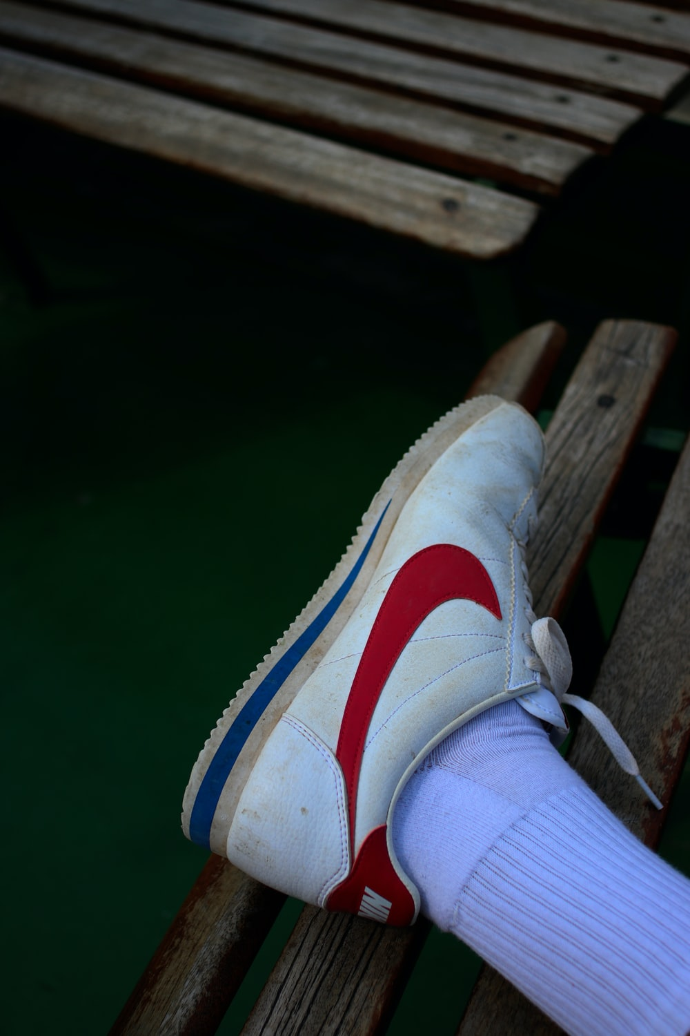 person wearing white and red with blue Nike sneaker