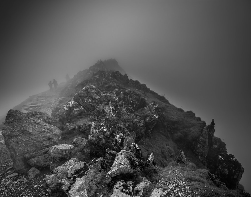 grayscale photography of mountain range in foggy day
