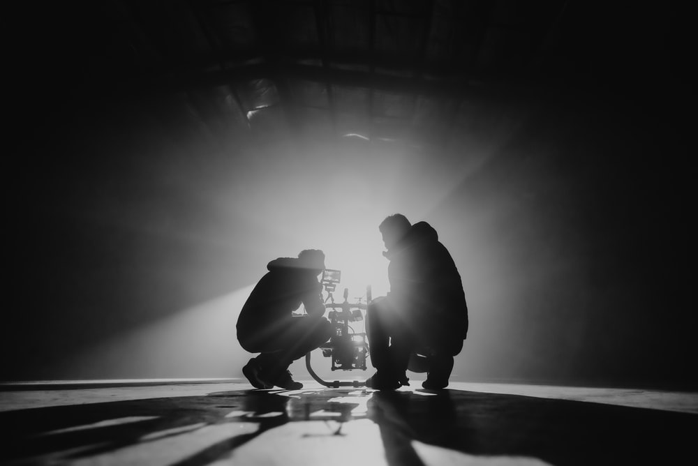 grayscale photography of two crouching men