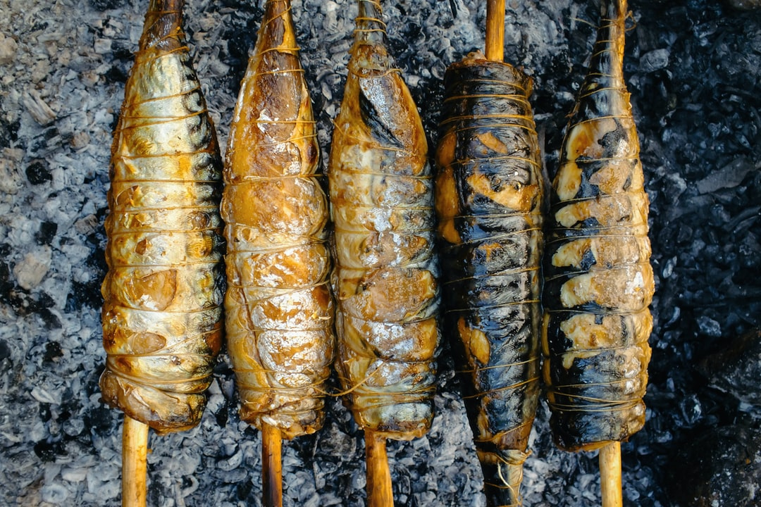 Barbecue, grill, kebab. Mackerel fish strung on wooden sticks and tied with string.