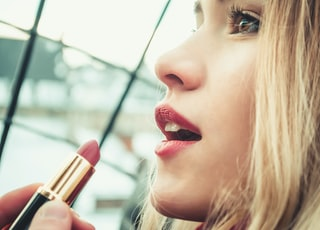 selective focus photography of woman holding lipstick