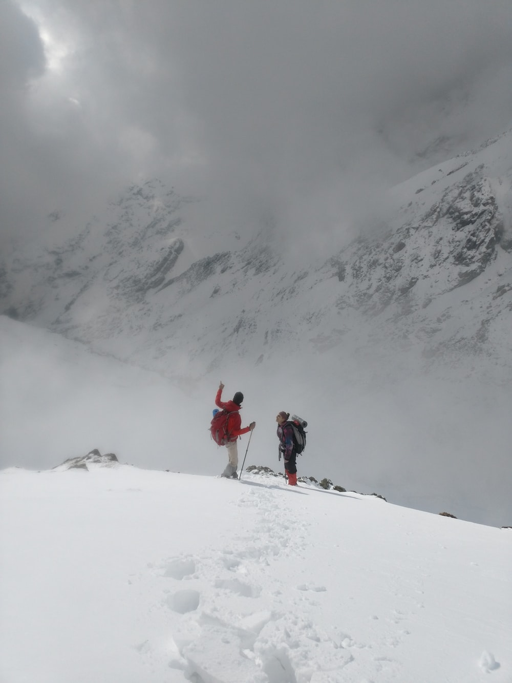 two people standing on snow-capped mountain