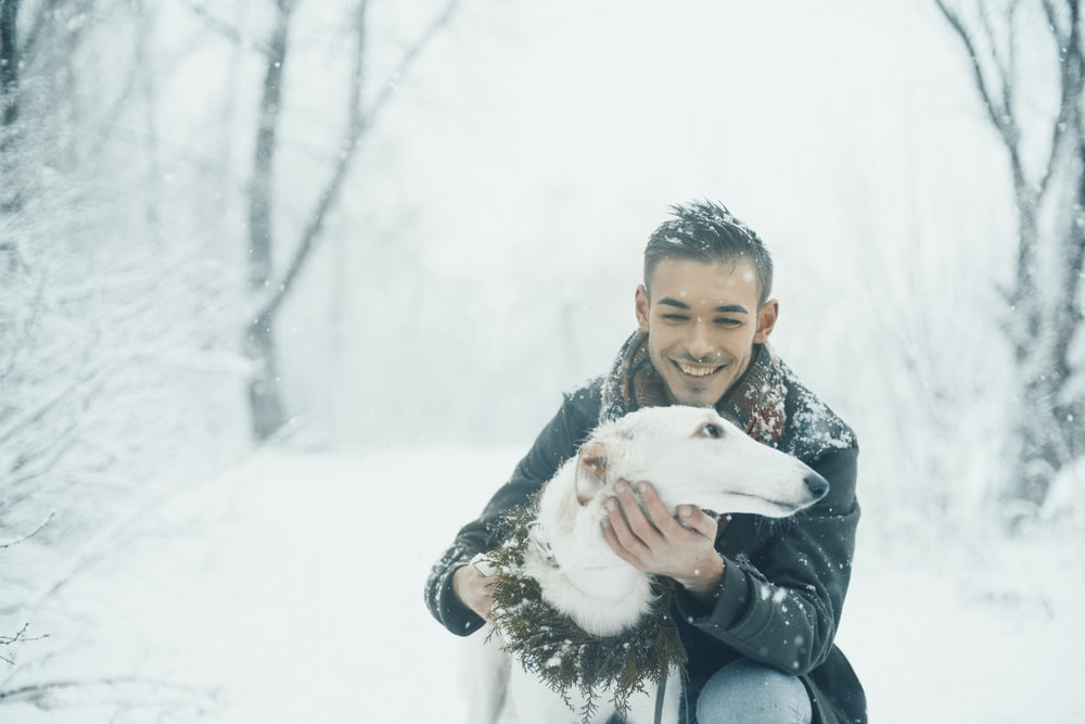man holding white dog