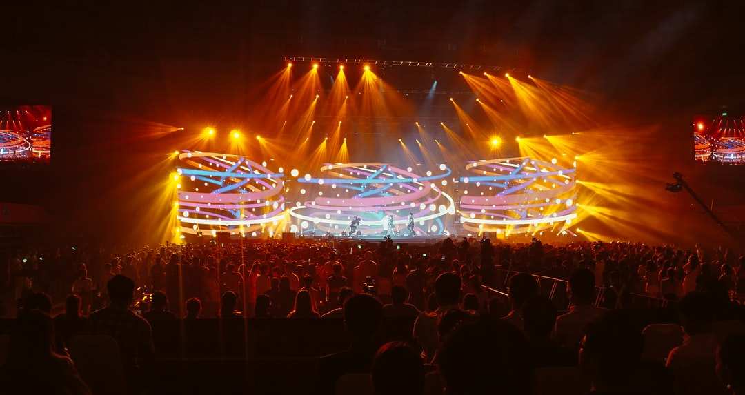 Crowd of young people enjoying a music concert with colorful stage lights