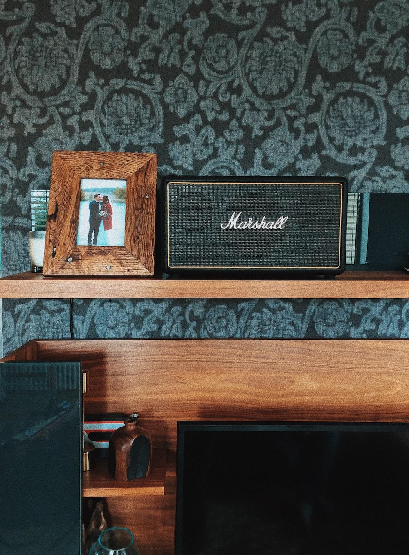 black Marshall speaker beside photo frame