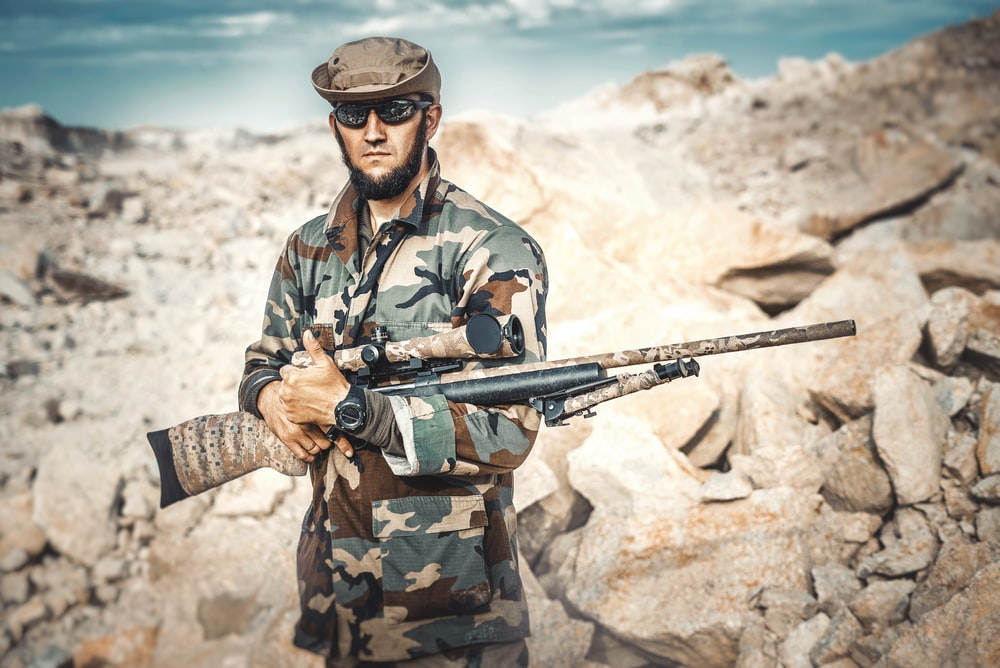 selective focus photography of standing man holding rifle