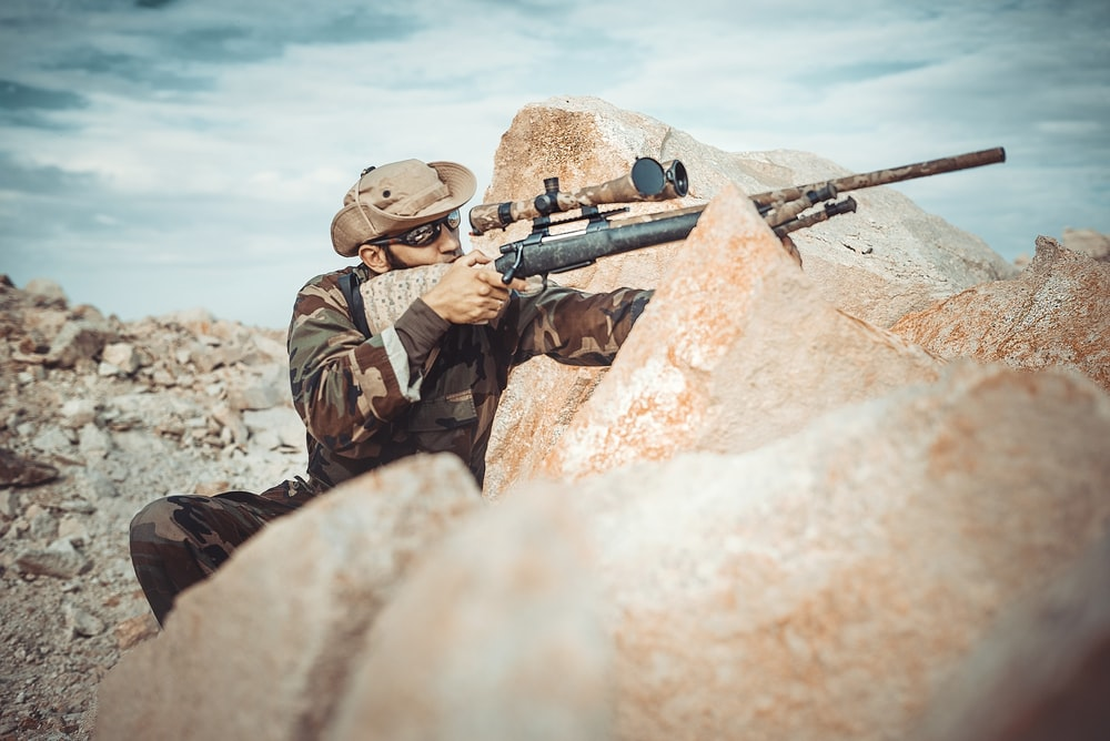 selective focus photography of man using rifle