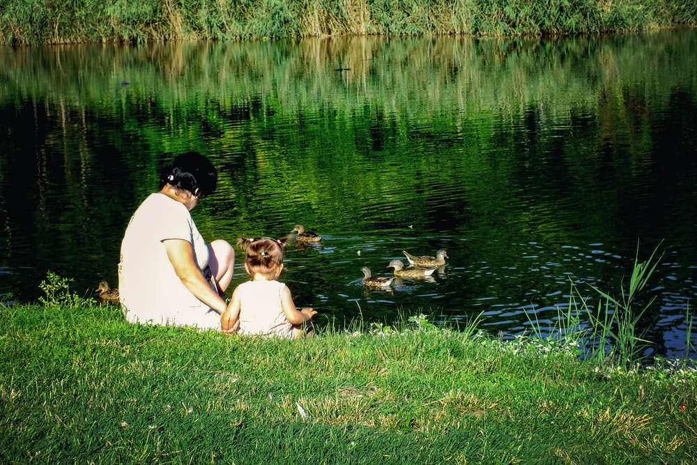 woman and girl near pond