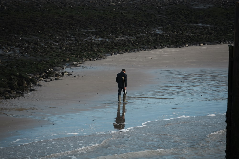 man walking on seashore