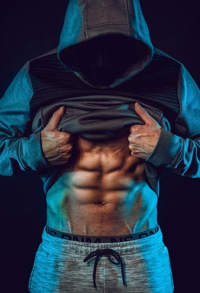 お腹を見せて腹筋を出している男性の画像