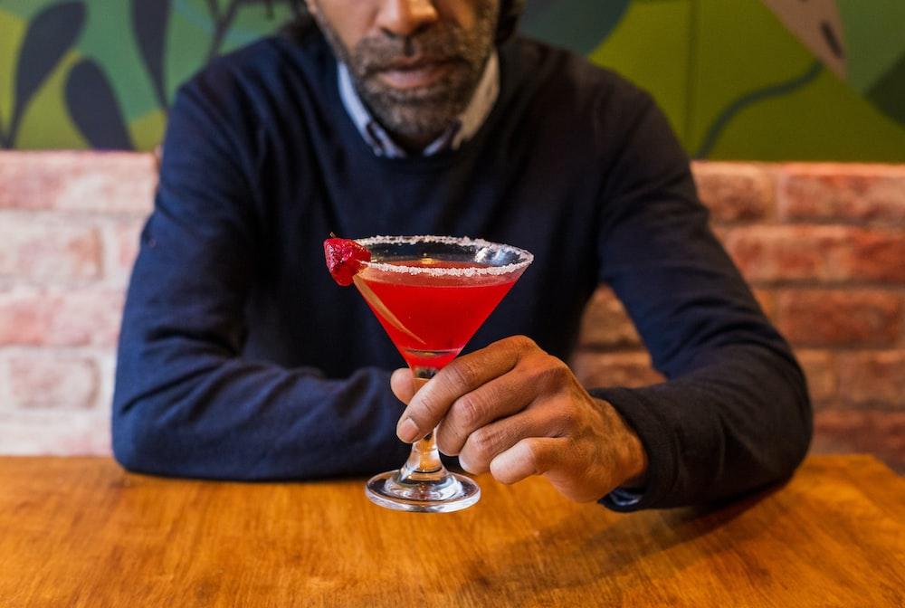 man holding martini glass