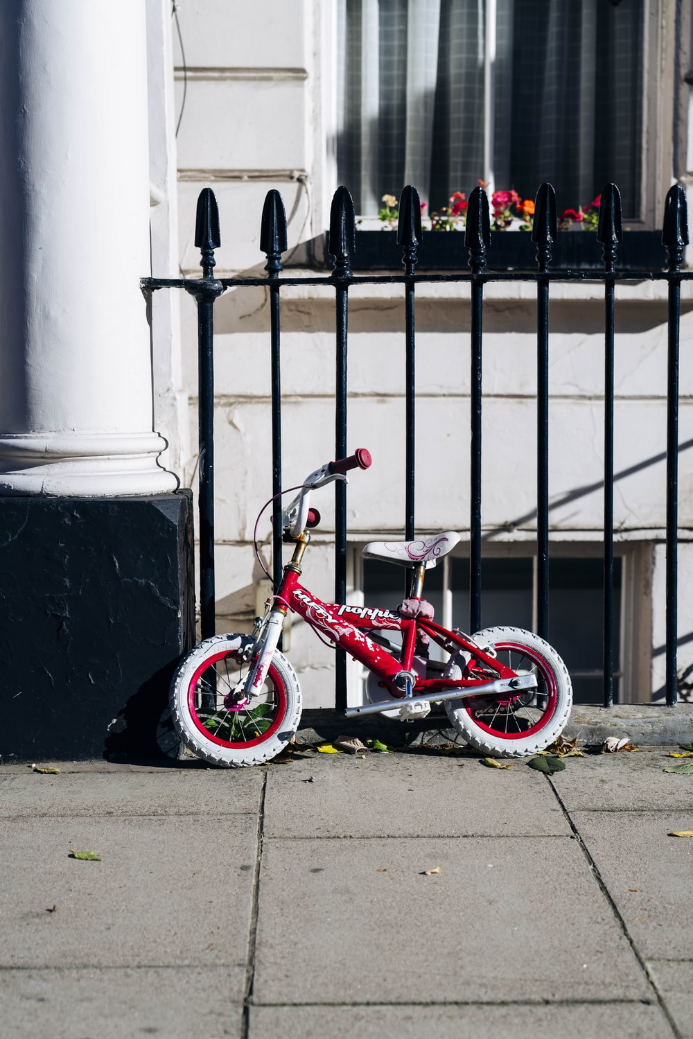 BMX bike parked beside fence and building during day