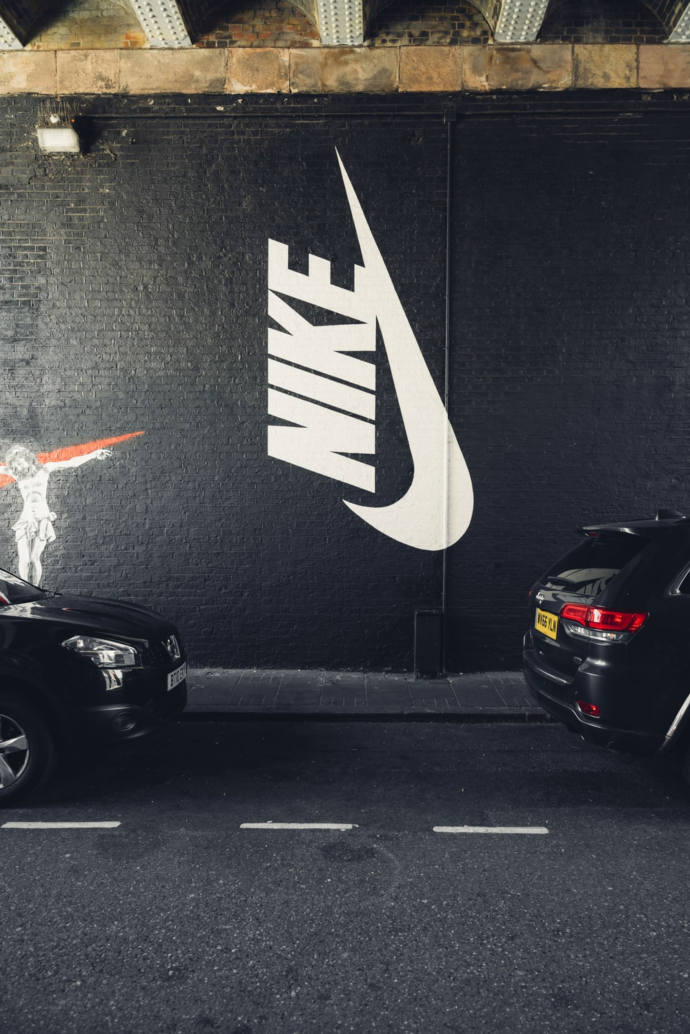 parked vehicles beside Nike wall