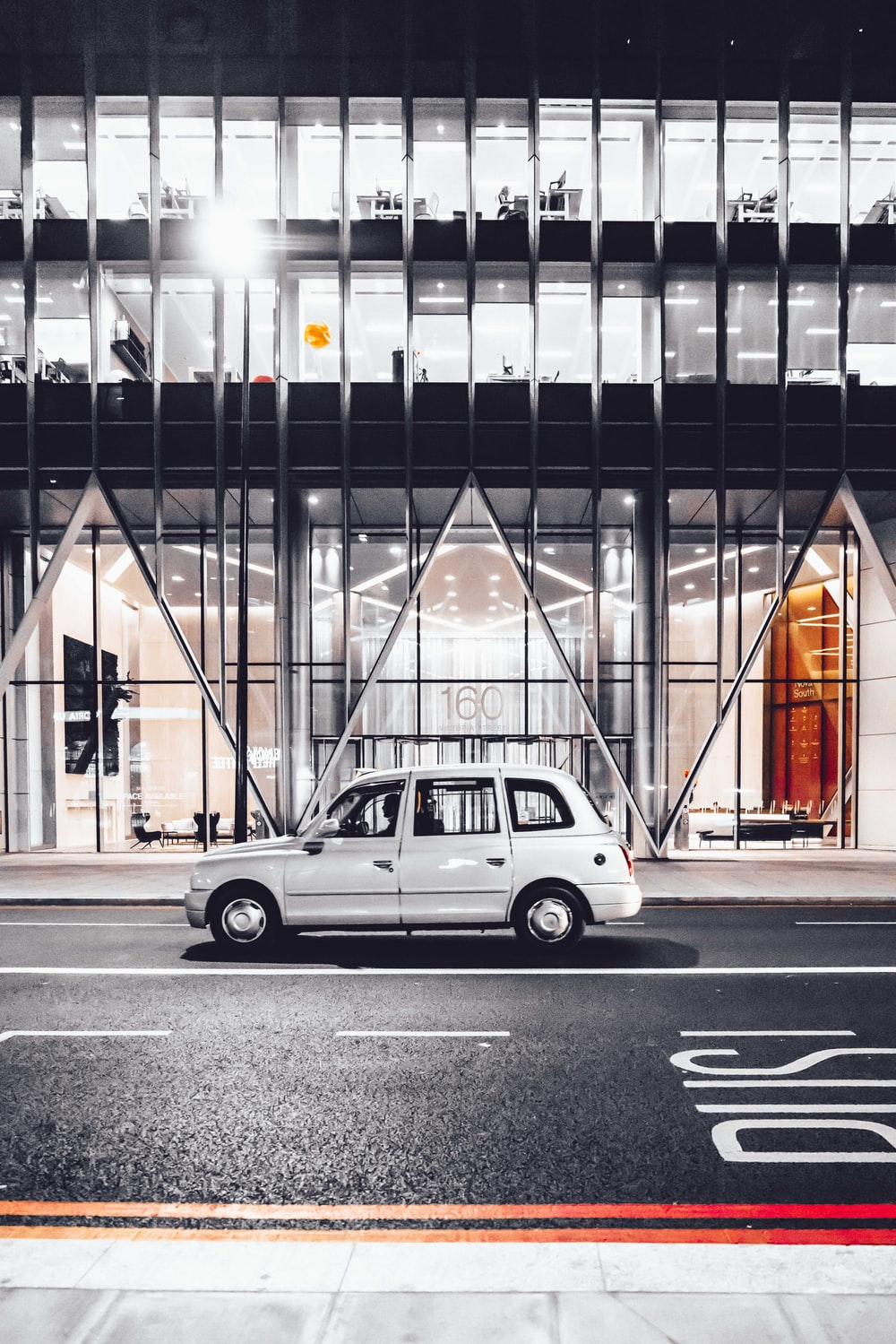 white 5-door hatchback on road near clear glass walled building