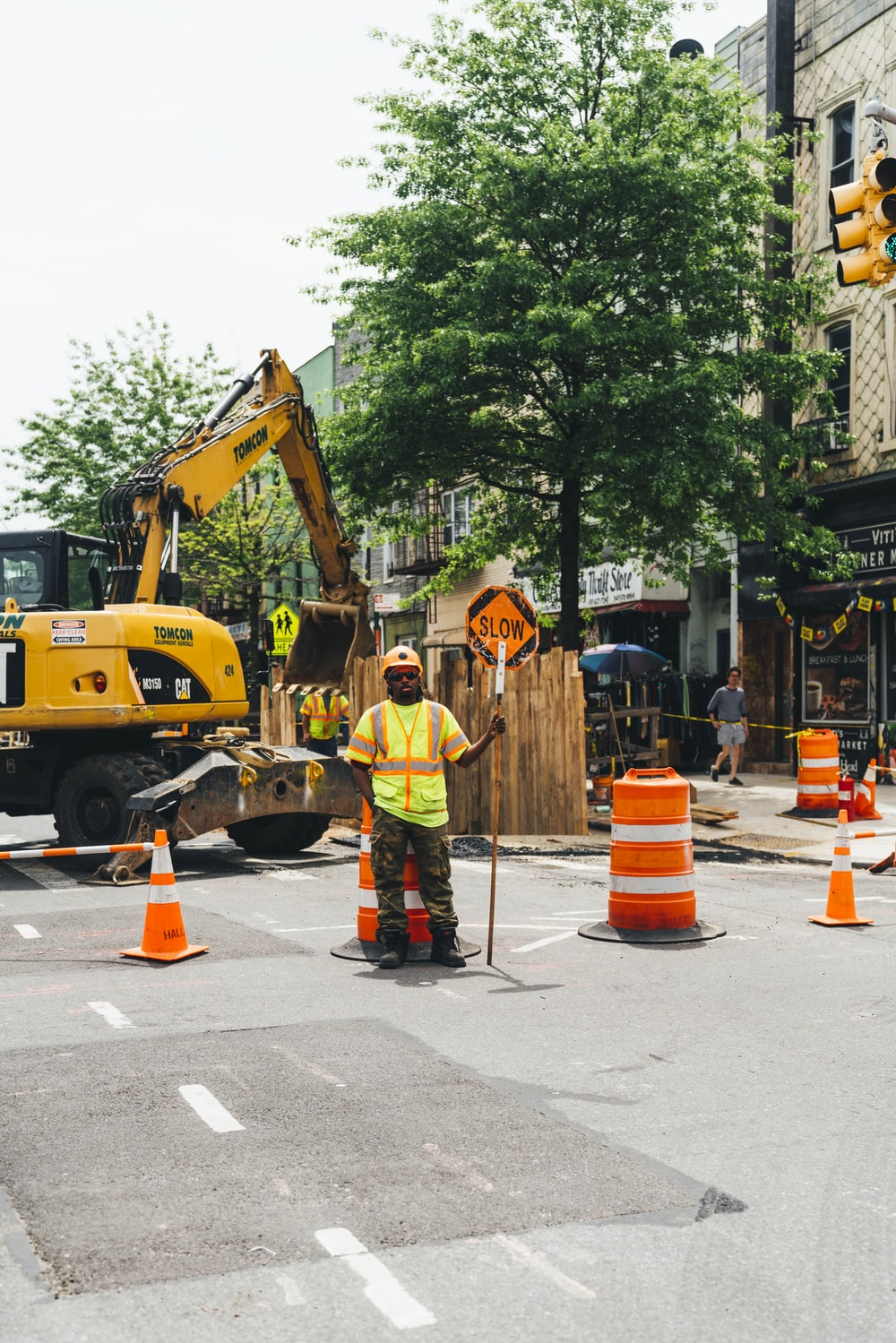 man wearing green reflective vest standing near traffic cones and backhoe