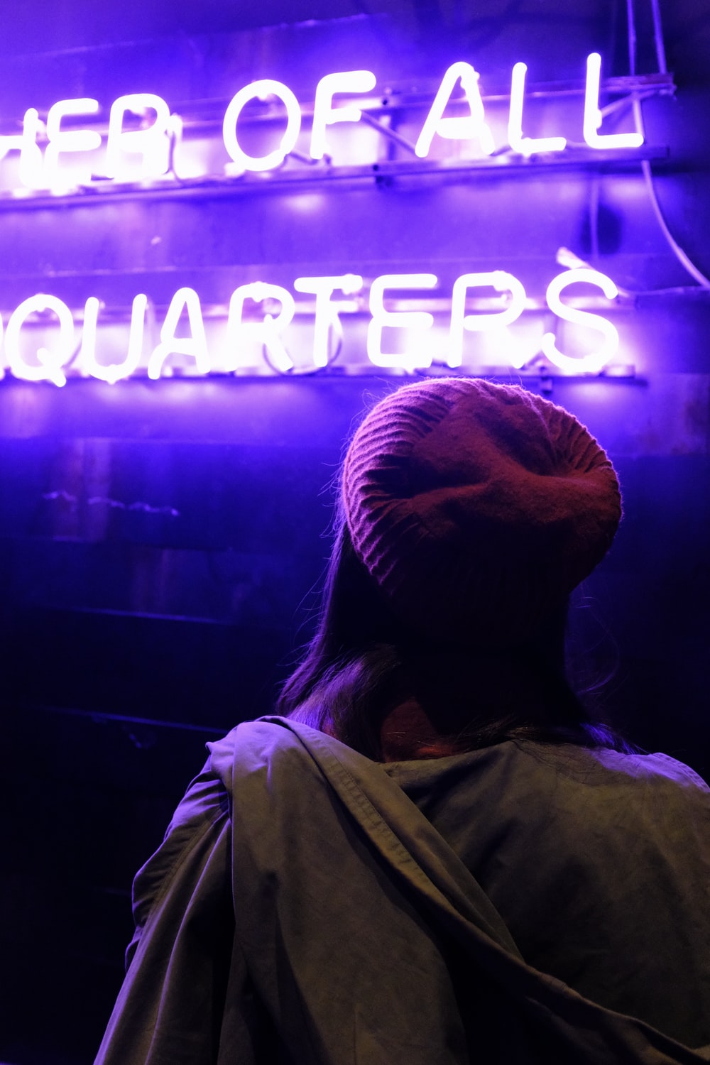 person wearing maroon knit cap in front of neon light signage
