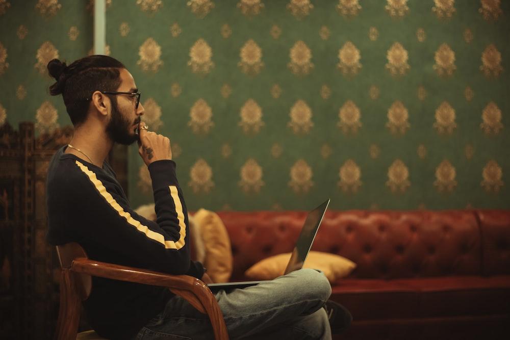部屋の中のソファの近くで彼の膝の上でラップトップを使用しながら椅子に座っている男