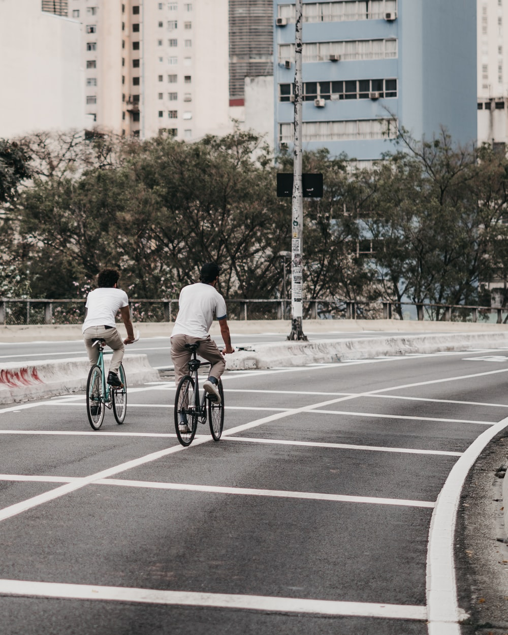 two men riding a bicycles