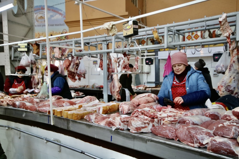 photography of women standing in front of meats
