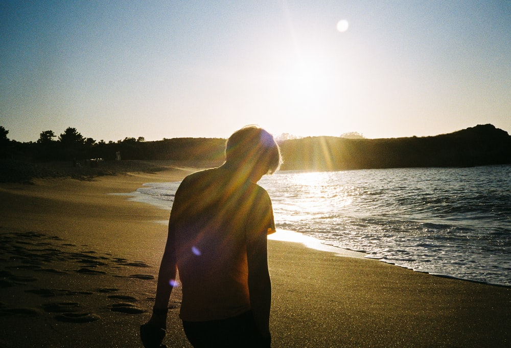 silhouette of person on seashore during daytime