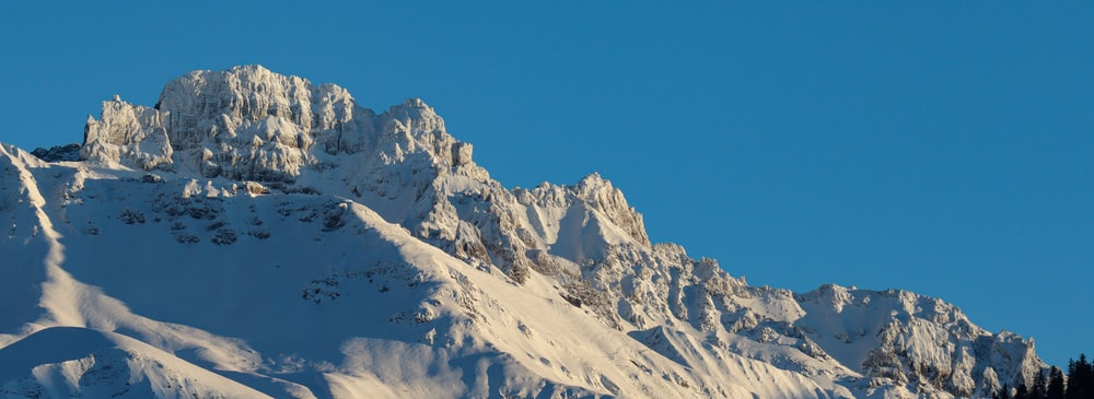 mountain covered by white snow during daytime