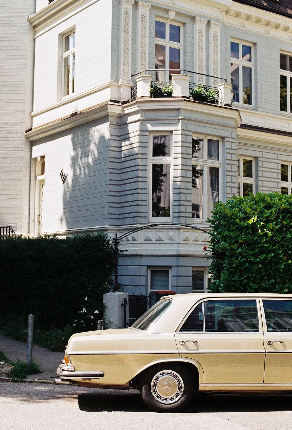 parked beige sedan beside house