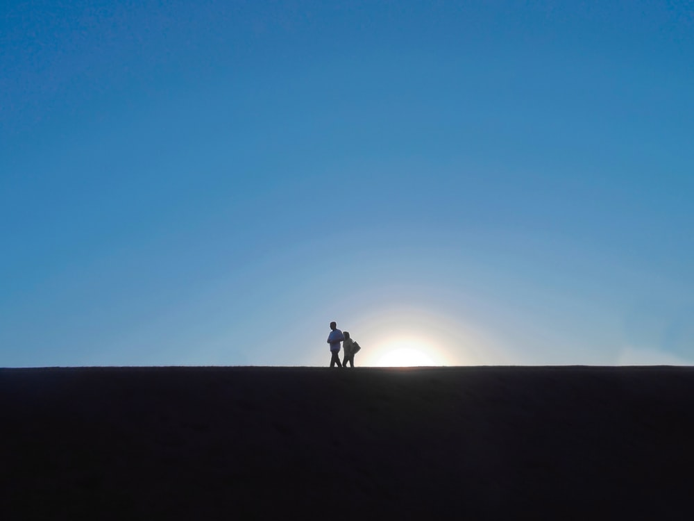 two people standing under blue sky