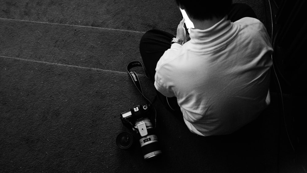 man sitting on stairs near DSLR camera