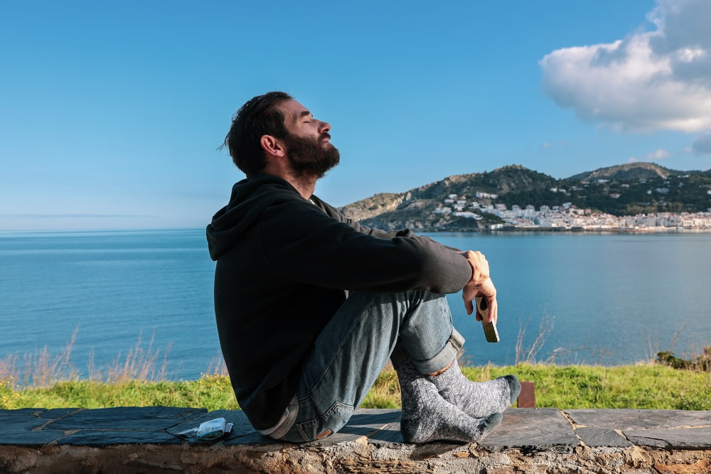 man sitting on a concrete bench overlooking the beach