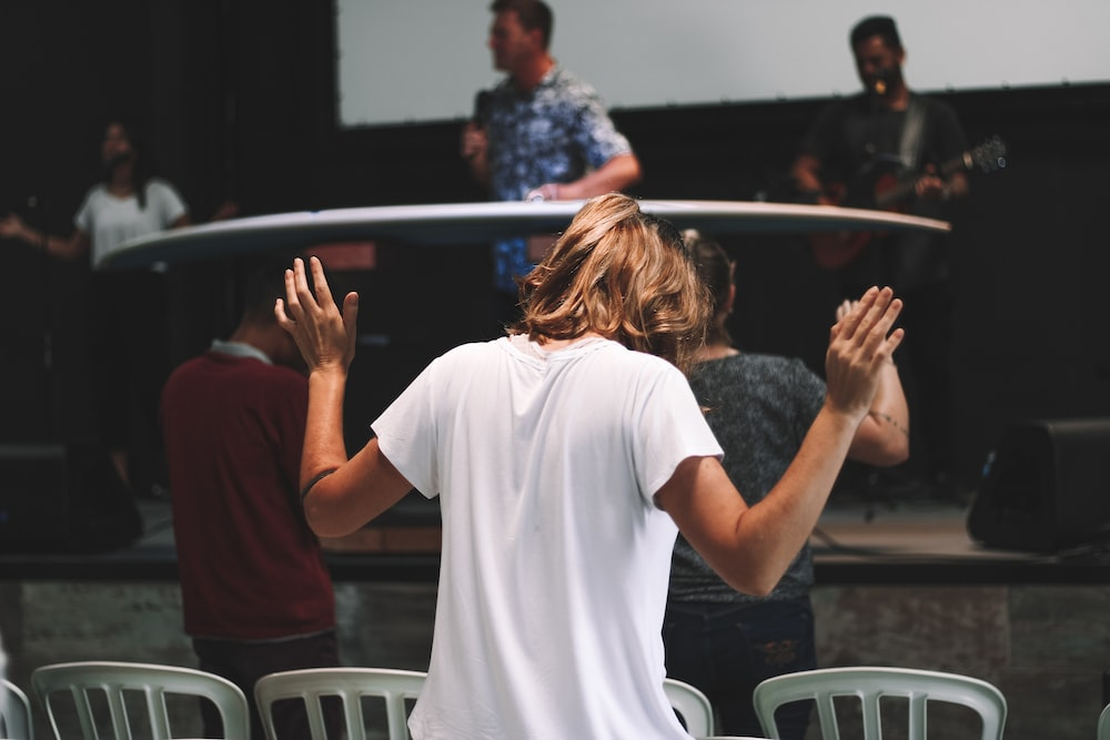 person wearing white shirt while raising hands