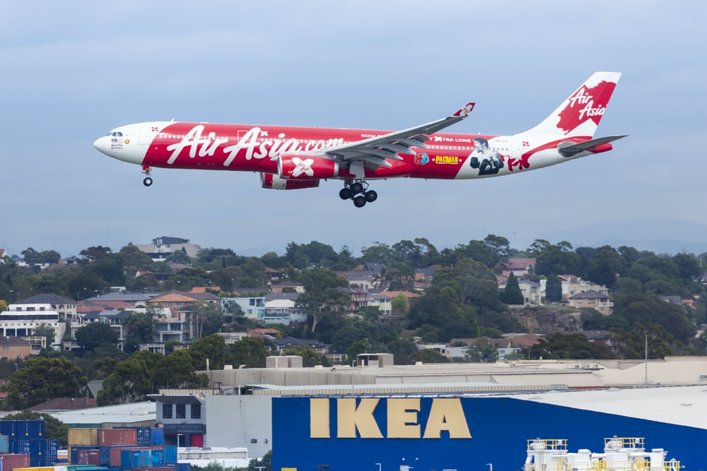 white and red Air Asia passenger plane above Ikea building during daytime