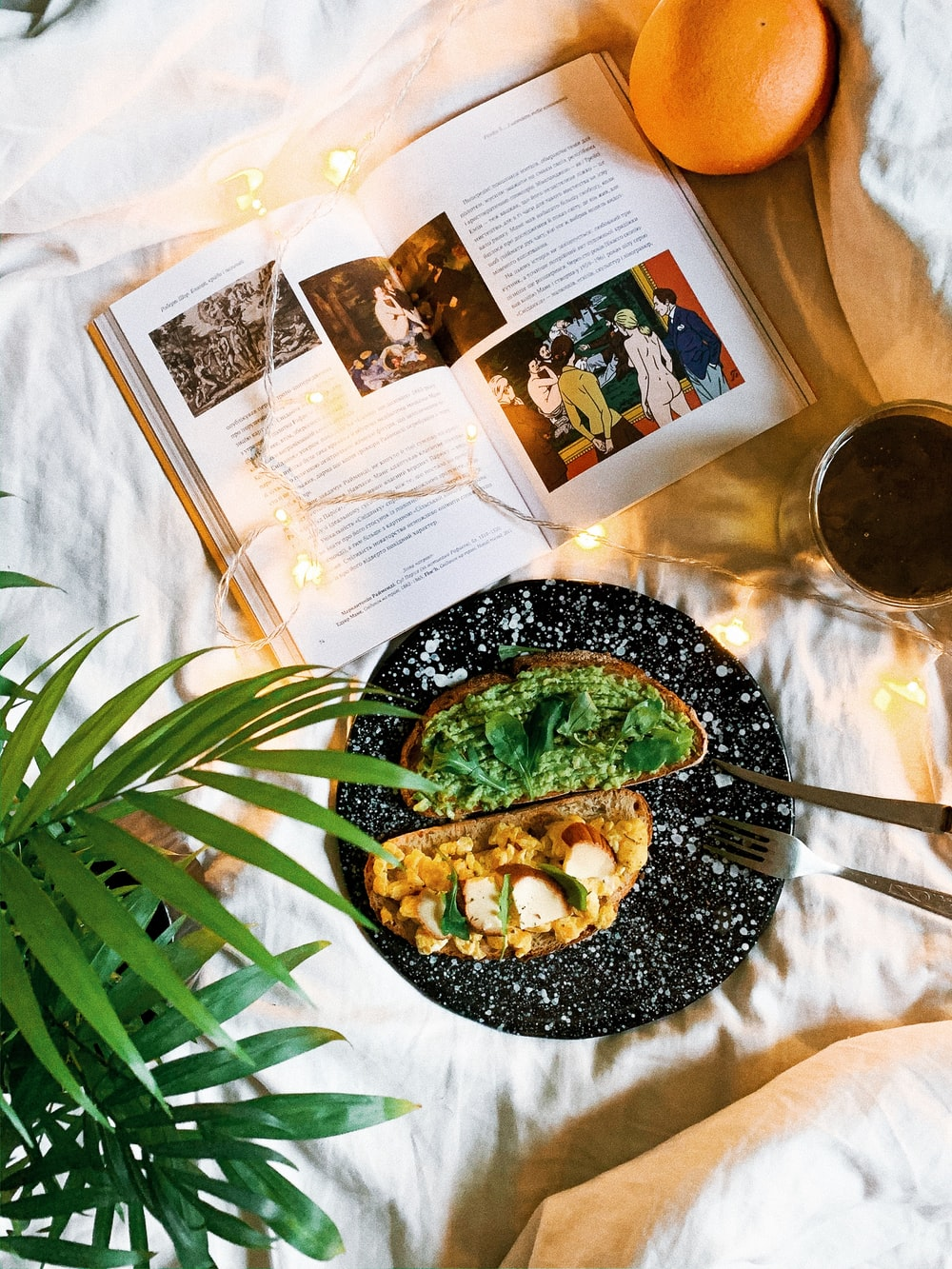 open book near bread with guacamole on top and glass of coffee