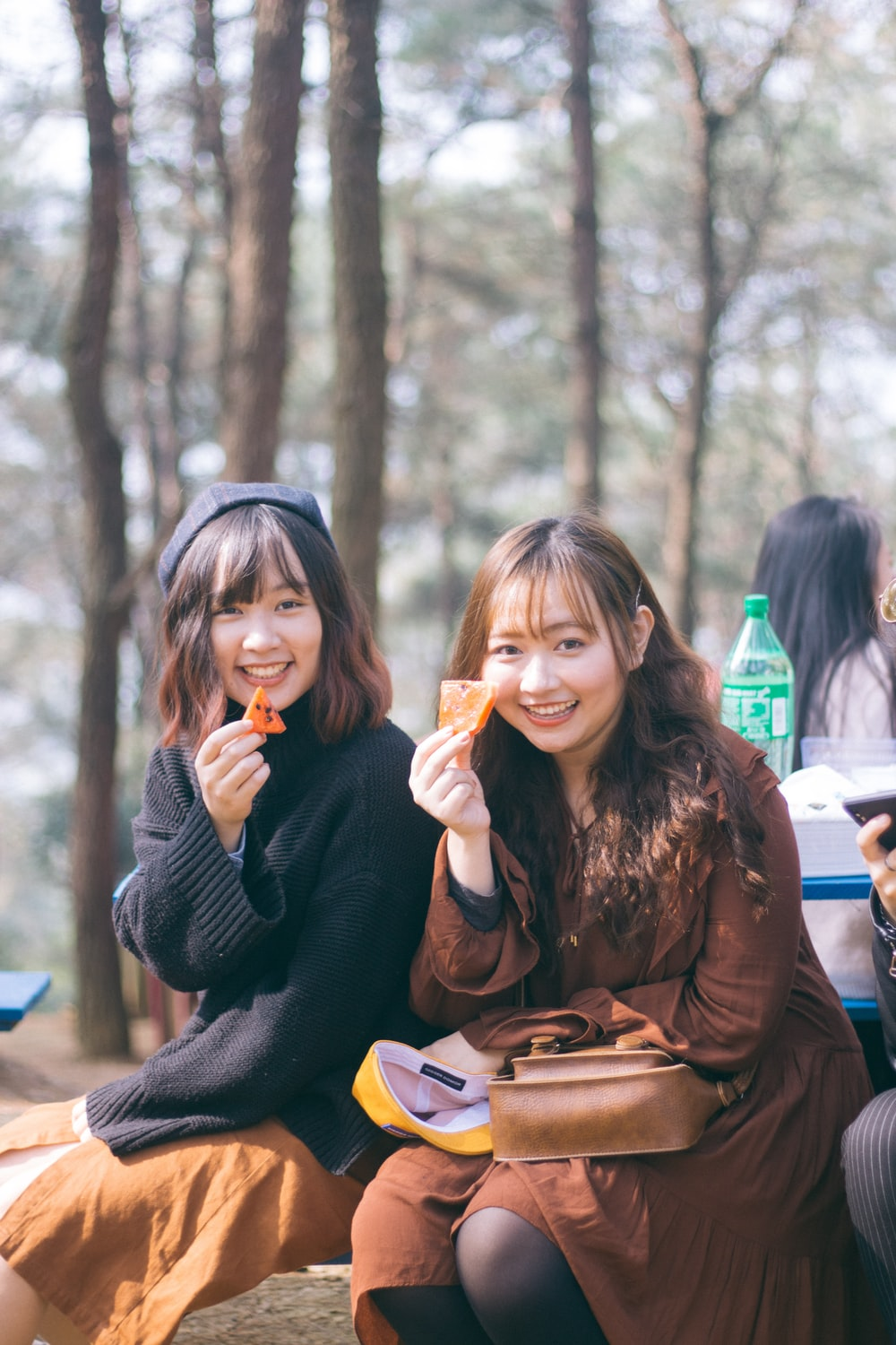 two women holding potato chips while sitting and smiling