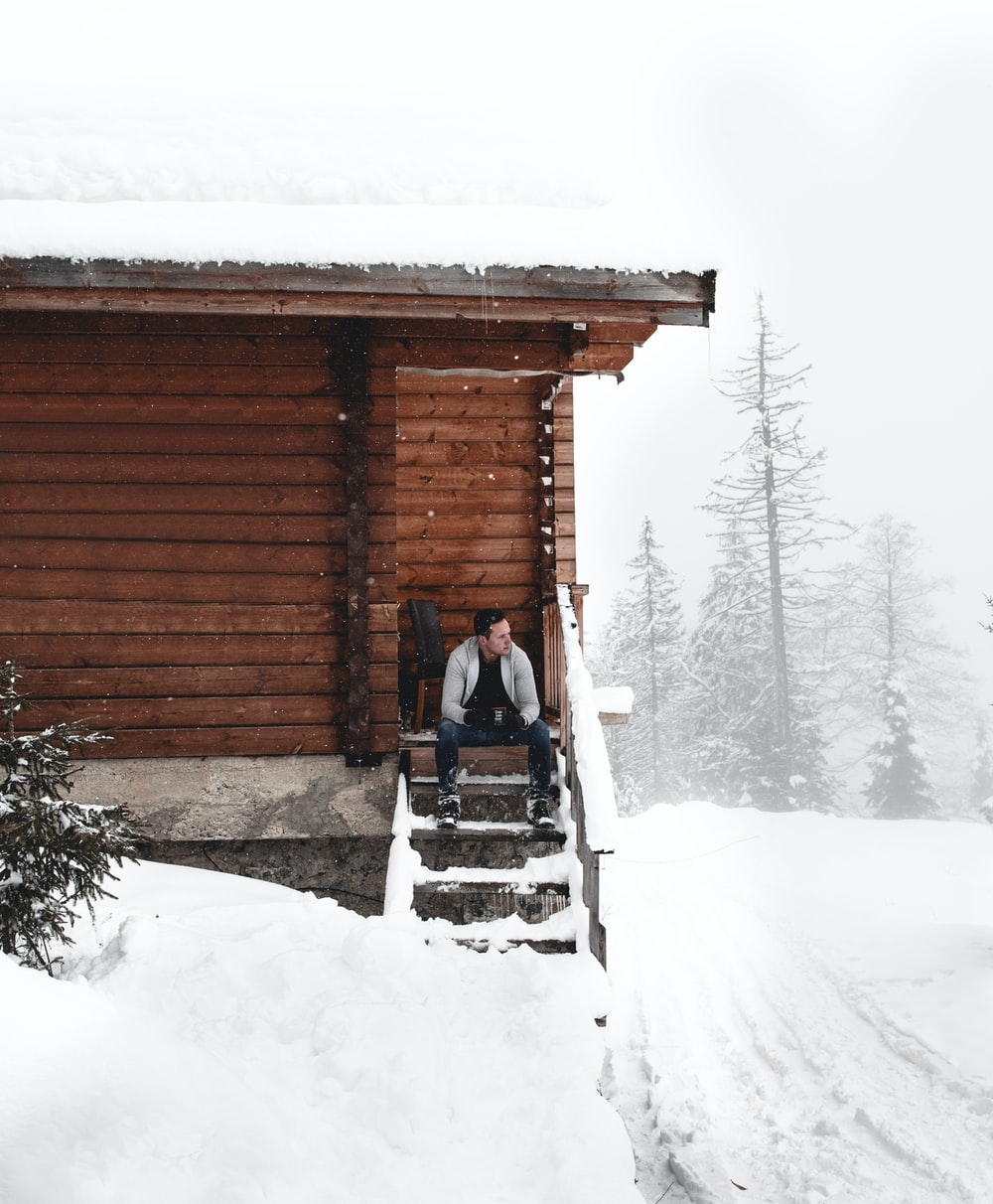man sitting on stairs during snow