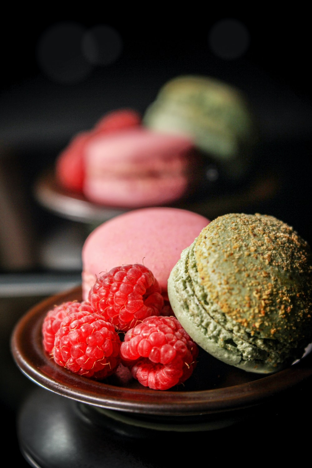 raspberries and French macaroons on plates