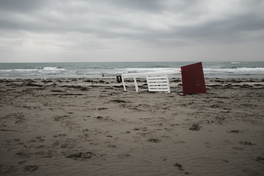white wooden table near seashore under white and gray sky