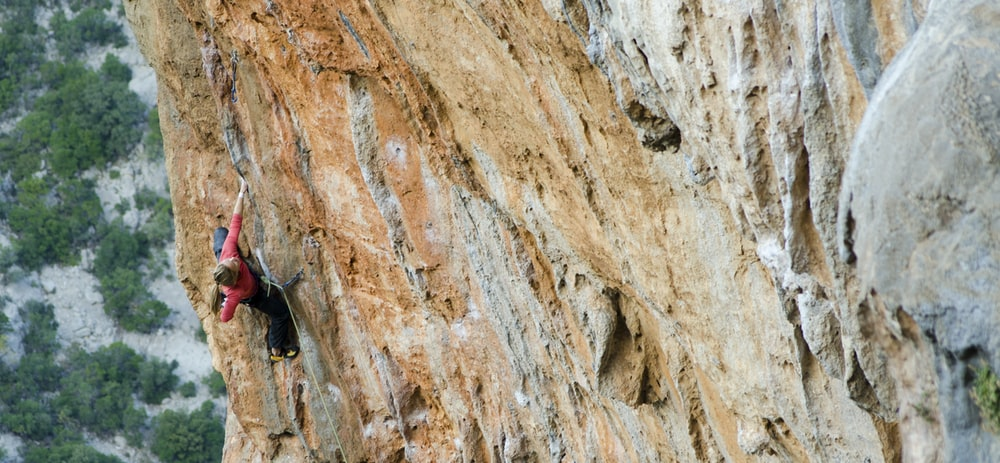 person climbing mountain during day