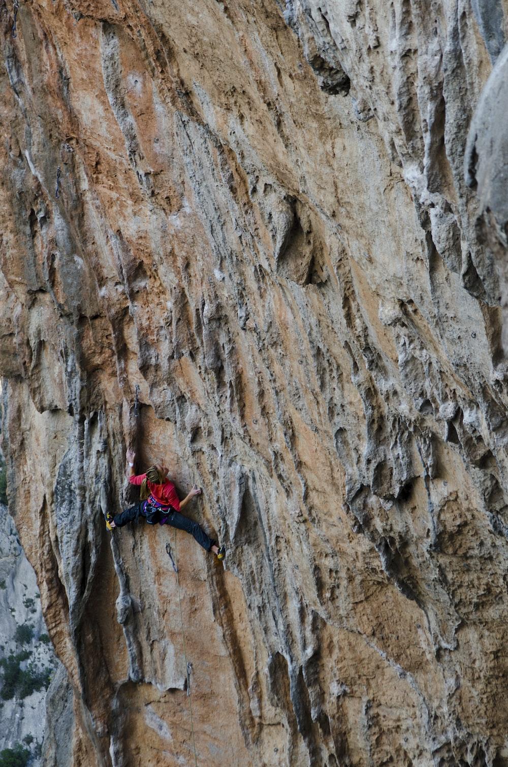 man climbing mountain during day