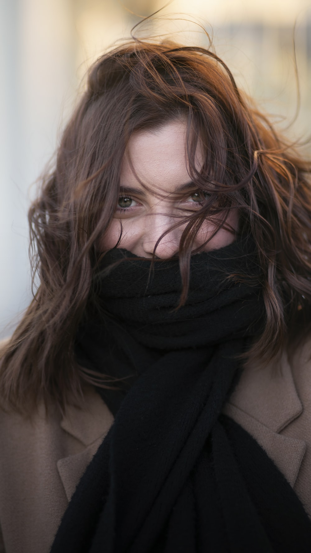 woman smiling and looking at the camera with scarf covering her mouth