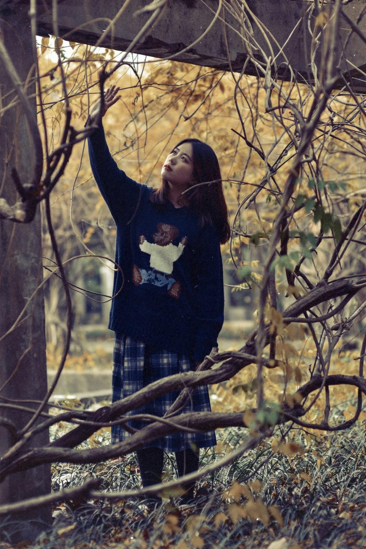 woman standing below bridge with vines