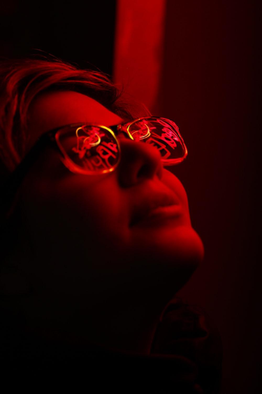 woman with eyeglasses in dim room