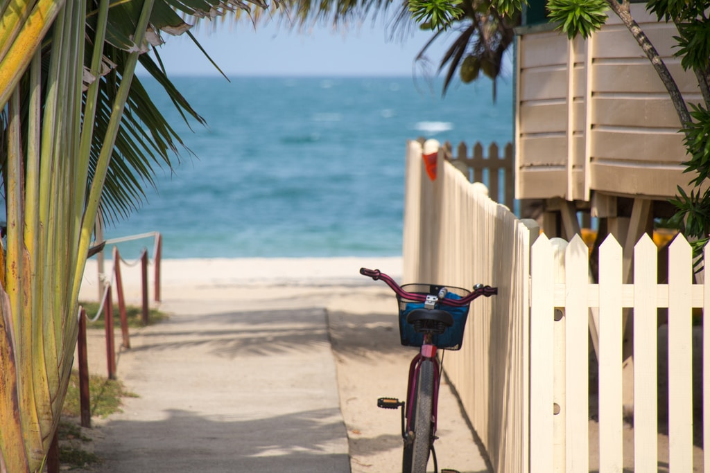 bike parks near white fence in front of the beach