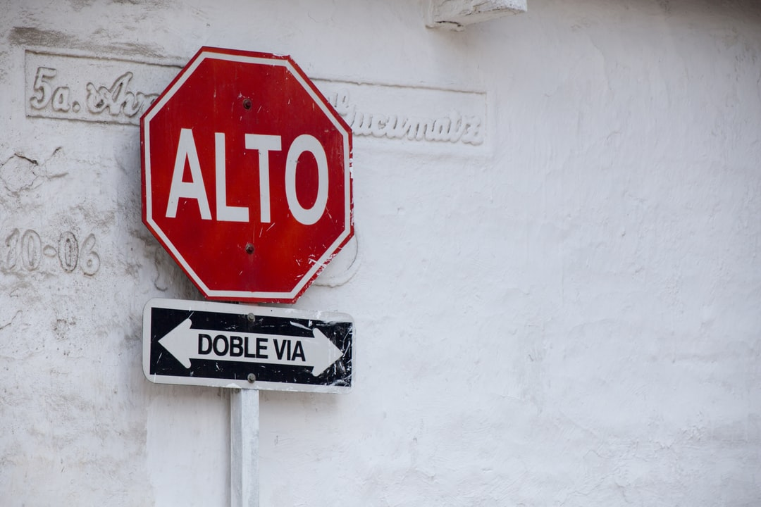 A Spanish stop sign and two-way street sign stands before a photogenic, rustic wall. En espanol. Señal de stop. Calle de doble sentido.