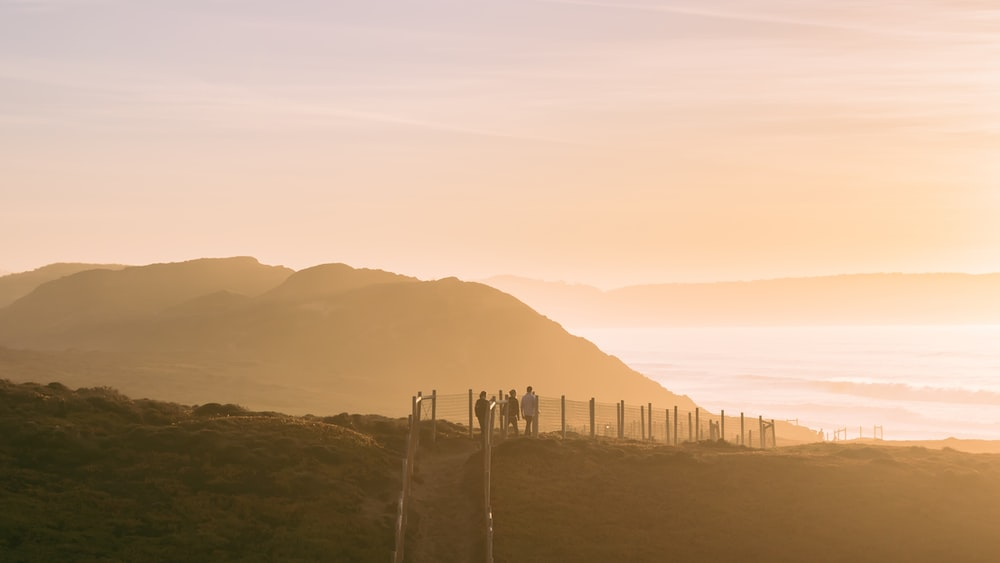 people on a mountain top during golden hour