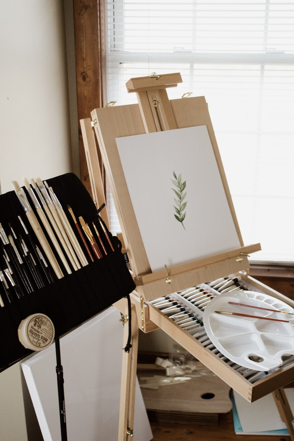 paint brushes beside a French easel and paint canvass
