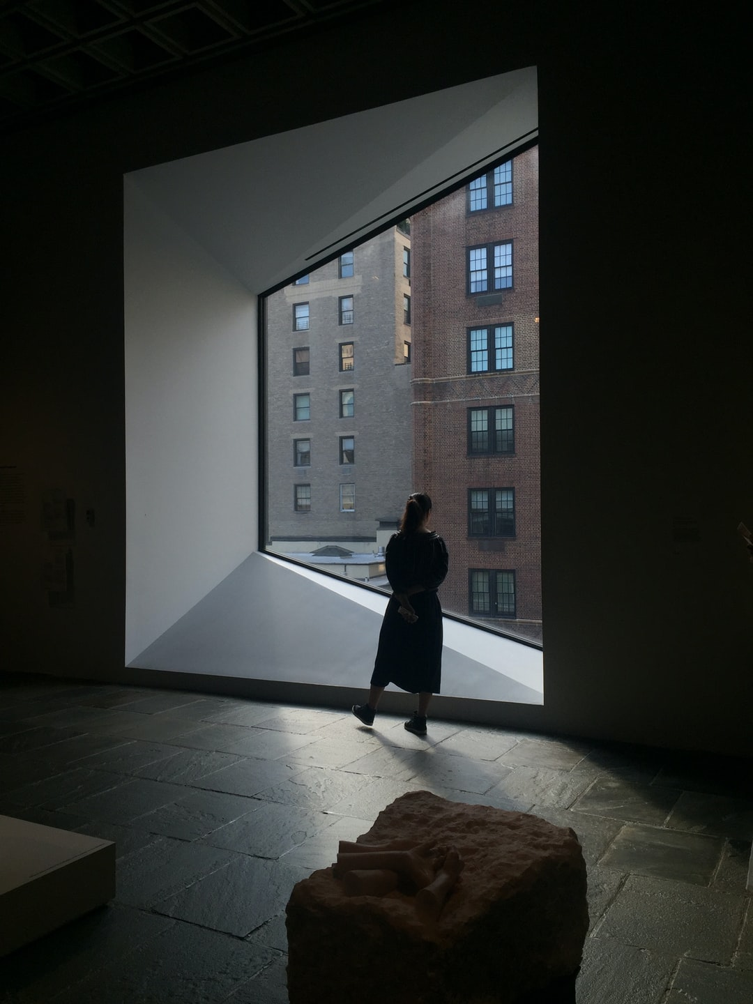 Woman starring at buildings through the window at the MET Museum, New York