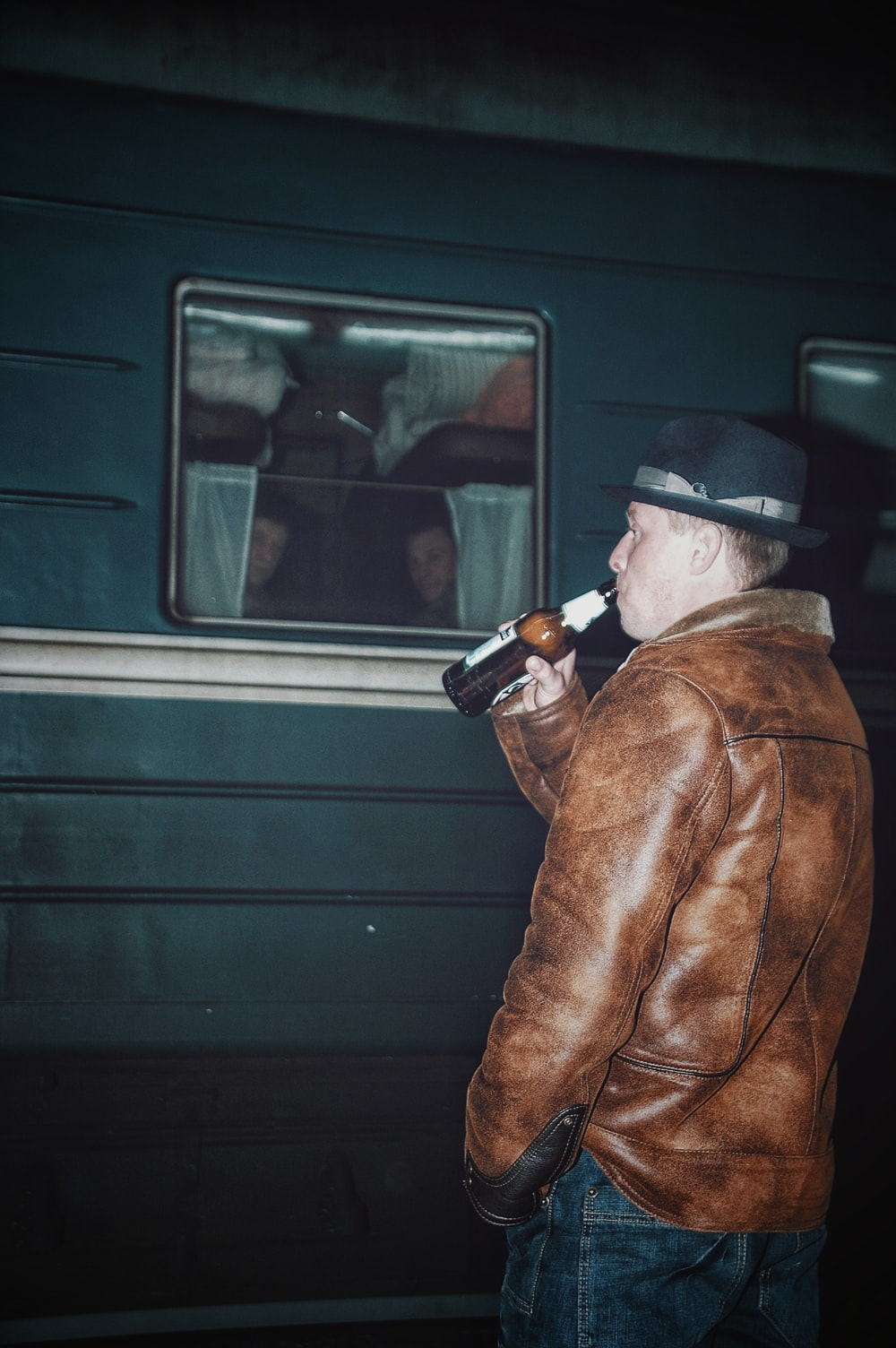 man wearing brown leather jacket drinking beer