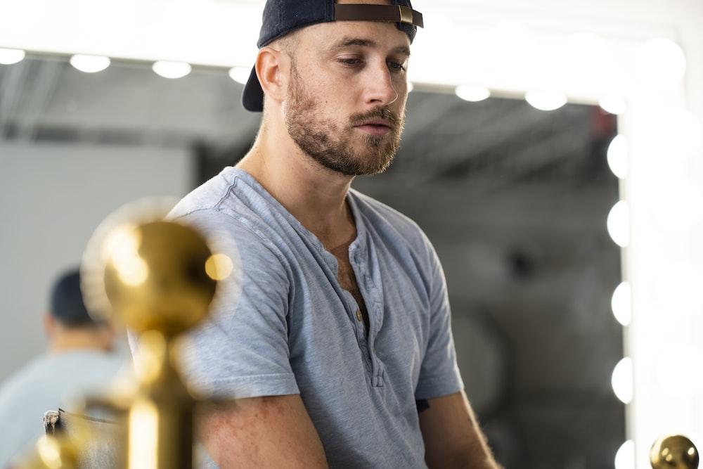 man wearing gray cap-sleeved shirt