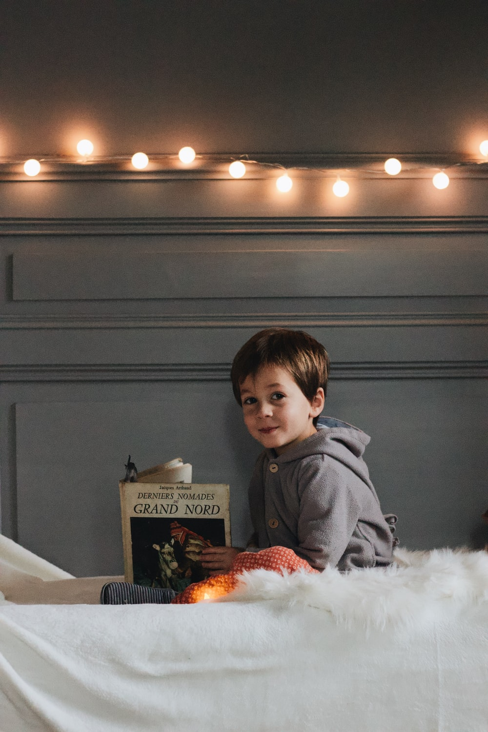 boy holding a book while sitting on top of bed
