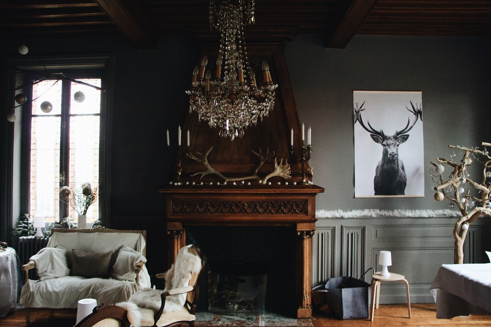 brown wooden fireplace beside a gray fabric sofa chair